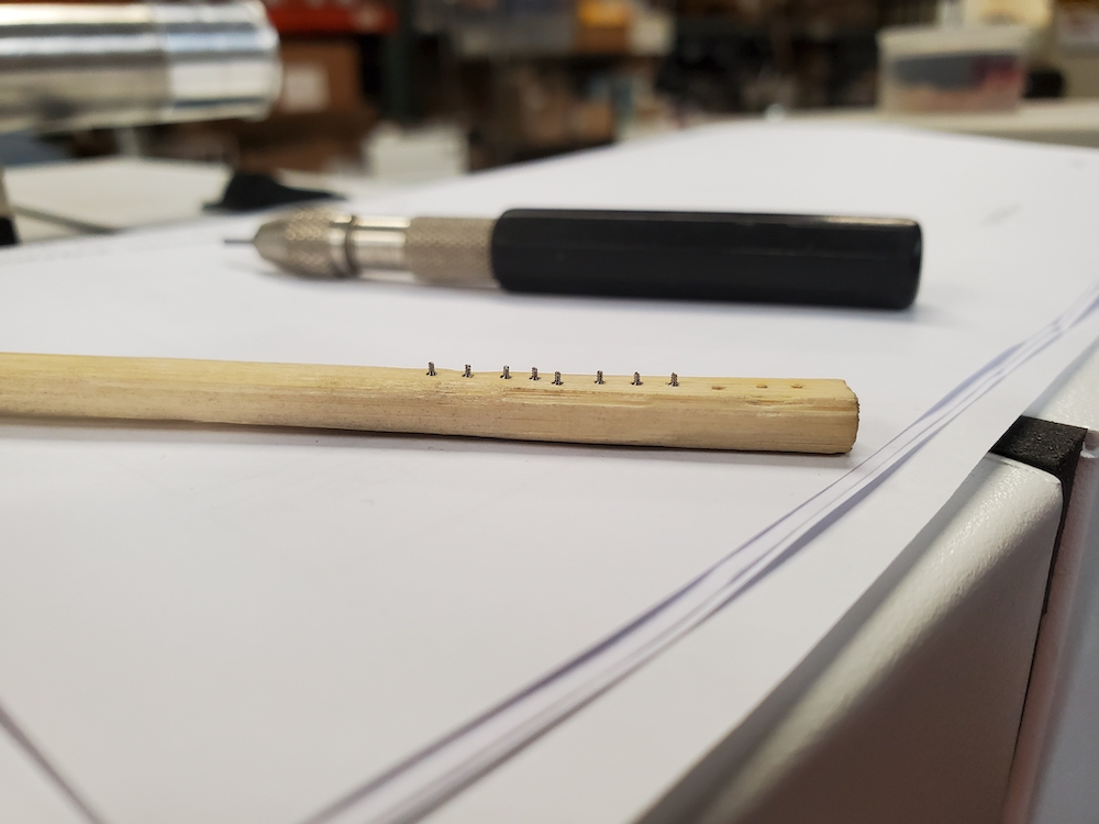 Bamboo chopstick with shallow holes holds the screws in place for micro abrasive processing